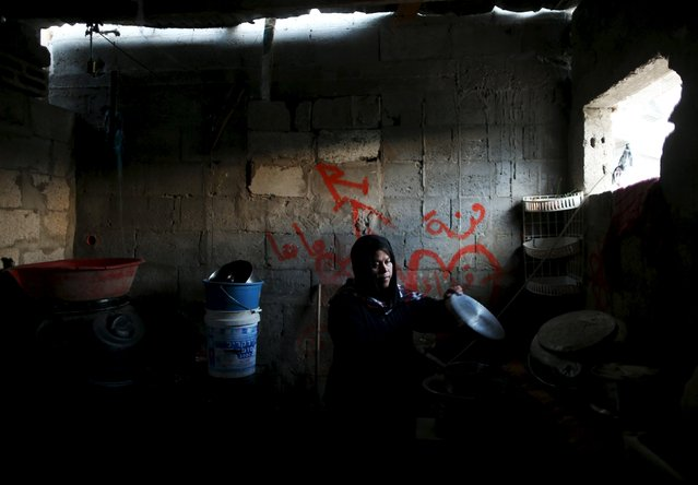 A Palestinian woman washes up in her kitchen during a power cut in the northern Gaza Strip March 25, 2015. (Photo by Mohammed Salem/Reuters)
