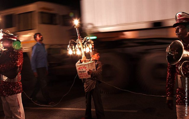 A young Indian boy holds a moving light as bandmasters wait for a wedding procession to start near Bijnor, Uttar Pradesh, India, April 18, 2012. The barat, a wedding procession with lights and music, is a very important part of countryside wedding celebrations