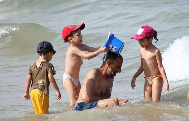 A man plays with his children in the sea on a hot day at La Goulette seaside in Tunis, Tunisia August 2, 2015. (Photo by Zoubeir Souissi/Reuters)