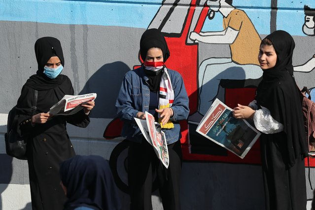 "Protesters read copies of ""Tuk Tuk"" newspapers, in Tahrir Square, Baghdad, Iraq, Wednesday, November 20, 2019. A small group of Iraqi volunteers is working in secrecy to produce the newspaper that aims to be the voice of the largest grassroots protest movement in the country's modern history. Its editors say the newspaper is vital amid shutdowns of the internet, filling a void left by mainstream Iraqi journalists who either back the government or fear retaliation. (Photo by Hadi Mizban/AP Photo)"