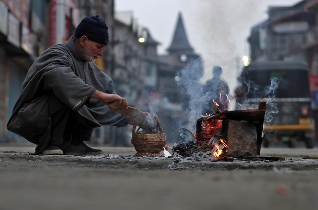 """A man fills hot coals in a """"Kangri"""", a traditional fire pot, after he warms himself up by a bonfire on a cold winter morning in Srinagar on January 2, 2020. (Photo by Danish Ismail/Reuters)"""