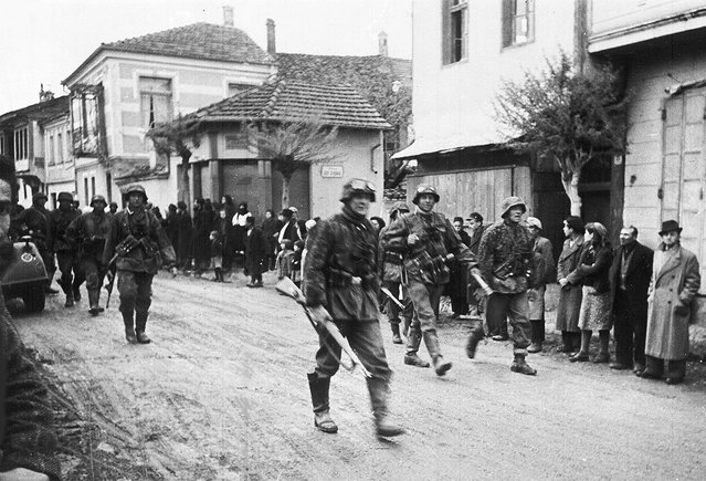 A squad of German soldiers pass through a Greek village, during the occupation of Greece, in May 1941