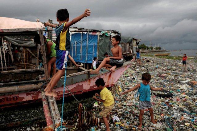Children play on a boat docked on the garbage-filled shore of Baseco Beach in Tondo, Manila, Philippines, July 30, 2019. (Photo by Eloisa Lopez/Reuters)