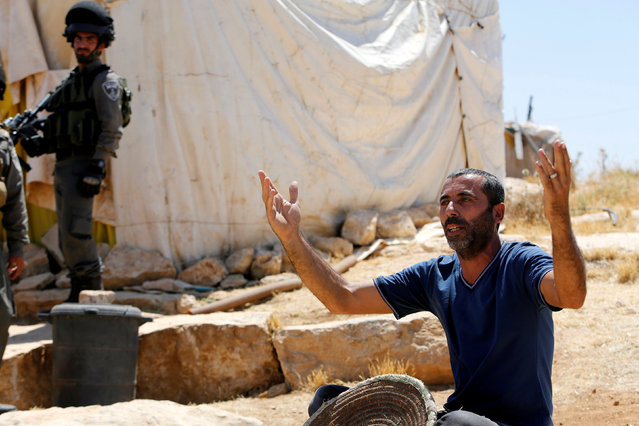 A Palestinian man reacts as Israeli troops demolish his shed near the West Bank village of Yatta, south of Hebron June 19, 2016. (Photo by Mussa Qawasma/Reuters)