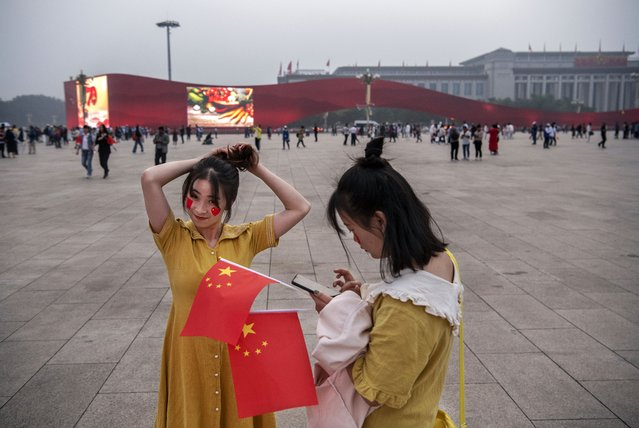 A Chinese woman adjusts her hair as a friend holds the national flag as they visit Tiananmen Square on September 27, 2019 in Beijing, China. China will mark the 70th anniversary of the founding of the People's Republic of China in 1949 on October 1st. (Photo by Kevin Frayer/Getty Images)