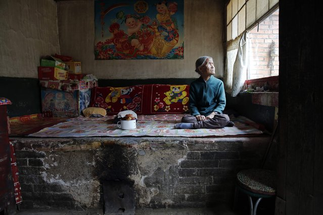 """Chinese former """"comfort woman"""" Zhang Xiantu rests on a traditional brick bed in her house in Xiyan Town, Shanxi Province, China, July 18, 2015. """"Comfort women"""" is the Japanese euphemism for women who were forced into prostitution and sexually abused at Japanese military brothels before and during World War Two. (Photo by Kim Kyung-Hoon/Reuters)"""