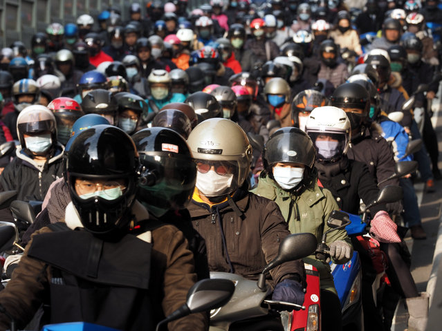 Taiwanese wearing face masks ride motorbikes in Taipei, Taiwan, 30 January 2020. The coronavirus, called 2019-nCoV, originating from Wuhan, China, has spread to all the 31 provinces of China as well as more than a dozen countries, including nine cases in Taiwan. The outbreak of coronavirus has so far claimed 170 lives and infected more than 8,000 others, according to media reports. (Photo by David Chang/EPA/EFE)