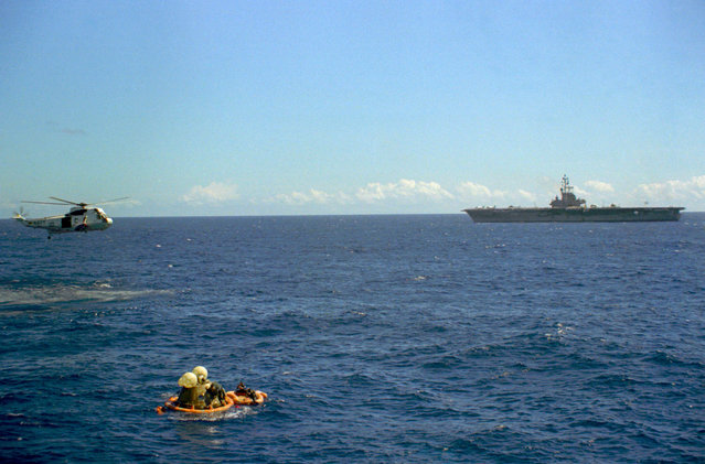 The Apollo 16 Command Module bobbles photographed in the waters of the central Pacific Ocean during recovery operations, on April 27, 1972. The prime recovery ship, USS Ticonderoga, is in the background. A recovery helicopter hovers overhead. (Photo by NASA)
