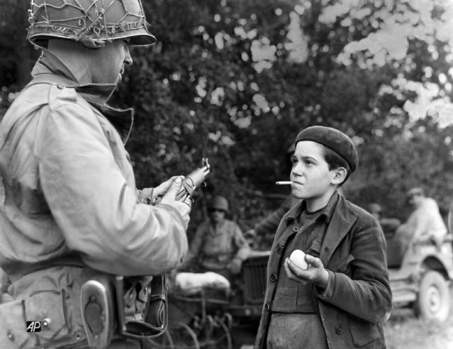 Pfc. Remy Bouchard swaps a cigarette for an egg with a French Orphan near La Haye Du Puits, France on July 18, 1944, which was captured by American forces. The boy is only twelve years old. (Photo by Hugh Broderick/AP Photo)