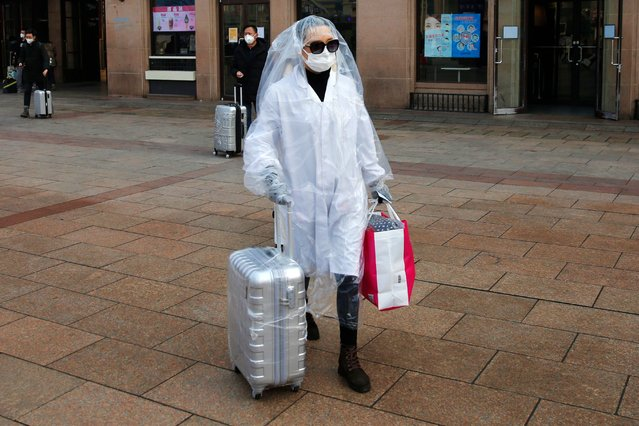 A passenger wearing protective mask and covering her body with plastic bags as protection from Coronavirus, at Beijing railway station in Beijing, China, 11 February 2020. The new study, conducted by prominent Chinese epidemiologist Zhong Nan-shan, shows the 2019 novel coronavirus (2019-nCoV) incubation period can be as long as 24 days, based on the recent analysis from about 1,000 confirmed patients in China. Media reports that the novel coronavirus (2019-nCoV), which originated in the Chinese city of Wuhan, has so far killed 1,017 people, infected 42,717 others, with 21,675 suspected cases mostly in China. (Photo by Wu Hong/EPA/EFE)