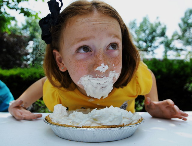 Isabella Fasula, 7, of Scranton, Pa., comes up for air while participating in a pie-eating contest Wednesday, July 23, 2014, during the annual Holy Family Residence Employee/Resident Carnival in Scranton. (Photo by Butch Comegys/AP Photo/The Scranton Times-Tribune)