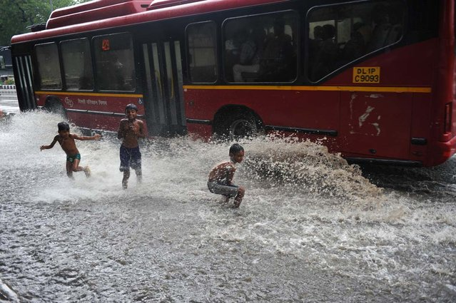 Indian children play in a water-logged street after a spell of monsoon rain in New Delhi on July 12, 2012