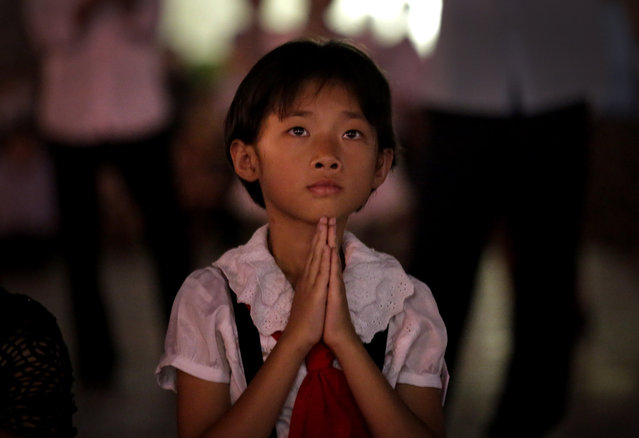 A North Korean girl watches as fireworks explode, Sunday, July 27, 2014 in central Pyongyang, North Korea. North Koreans gathered at Kim Il Sung Square to watch a fireworks display as part of celebrations for the 61st anniversary of the armistice that ended the Korean War. (Photo by Wong Maye-E/AP Photo)