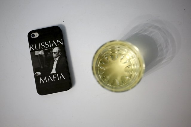 """A mobile phone cover with a picture of Russian President Vladimir Putin which reads """"Russian Mafia"""" is seen in this photo illustration taken in a hotel room in Kazan, Russia, August 5, 2015. (Photo by Stefan Wermuth/Reuters)"""