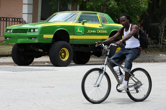 A man rides his bicycle past a heavily modified car with a John Deere logo in Orlando, Florida, U.S., June 20, 2016. (Photo by Carlo Allegri/Reuters)