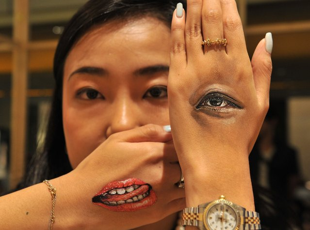 """A woman displays body-paintings of her eye and her mouth on the back of her hands after Japanese body-painting artist Hikaru Cho (unseen in this picture) painted at an art event called """"Future en-nichi"""" in Tokyo on August 6, 2014. En-nichi is a popular Japanese summer festival and 12 contemporary artists exhibit through to August 10. (Photo by Yoshikazu Tsuno/AFP Photo)"""