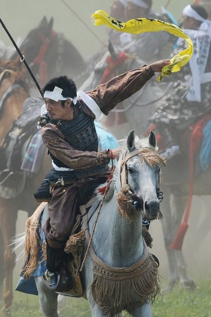 """A local man in samurai armor riding his horse waves as he catches a yellow sacred flag at the annual Soma Nomaoi Festival in Minamisoma, Fukushima Prefecture, on July 29, 2012. Some 400 horses and thousands of people took part in the 1,000-year-old """"Soma Nomaoi"""", or wild horse chase, at the weekend in the shadow of Japan's crippled Fukushima nuclear plant. (Photo by Toru Yamanaka/AFP Photo)"""
