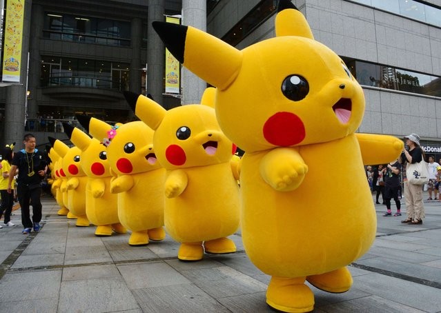 "Dozens of Pikachu characters, the famous character of Nintendo's videogame software Pokemon, parade at the Landmark Plaza shopping mall in Yokohama, suburban Tokyo on August 14, 2014. The Pikachu mascots walk around daily to attract summer vacationers as a part of the ""Great Pikachu Outbreak"" event through the weekend. (Photo by Yoshikazu Tsuno/AFP Photo)"