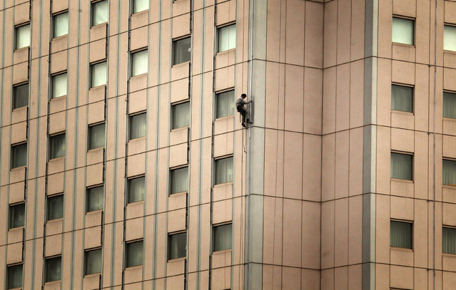 A cleaner abseils down the side of a newly renovated building in central Beijing March 5, 2012. (Photo by David Gray/Reuters)