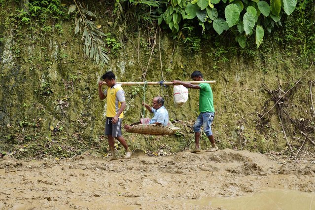 Indian youths carry an old man in a basket along a road covered in mud, after heavy monsoon rains made roads impassable for traffic north of Karimganj, in the northeastern state of Assam, on July 20, 2016. (Photo by AFP Photo/Stringer)