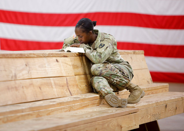 Specialist Cerelai Spencer from Spring Lake, North Carolina, reads her bible while waiting for her unit from the 602nd Area Medical Support Company to depart for St. Thomas in the U.S. Virgin Islands, at Fort Bragg, North Carolina, U.S., September 13, 2017. (Photo by Jonathan Drake/Reuters)