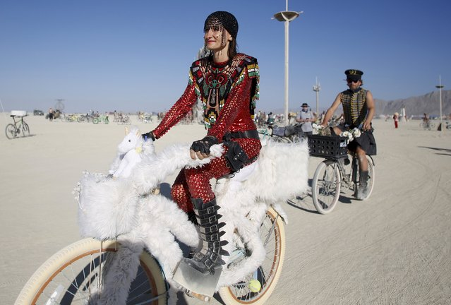 "Bibi rides her bike on the Playa during the Burning Man 2015 ""Carnival of Mirrors"" arts and music festival in the Black Rock Desert of Nevada, August 31, 2015. (Photo by Jim Urquhart/Reuters)"