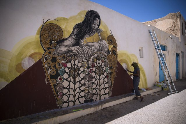 """US artist Monica Canilao decorates a wall in the village of Erriadh, on the Tunisian island of Djerba, on August 7, 2014, as part of the artistic project """"Djerbahood"""". (Photo by Joel Saget/AFP Photo)"""