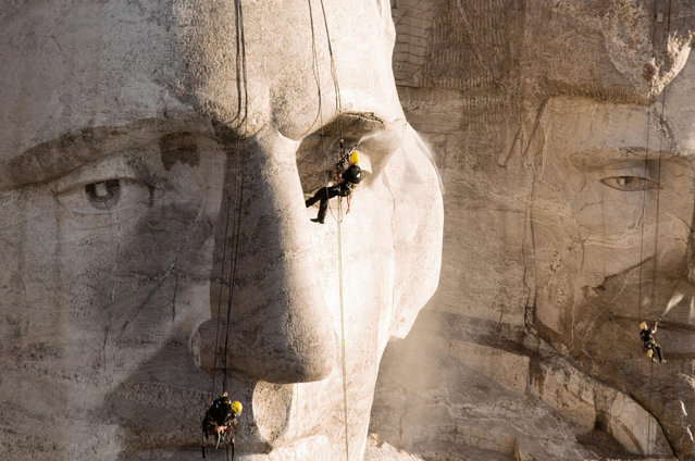 Two men cleaning Mount Rushmore in South Dakota. (Photo by Caters News Agency)