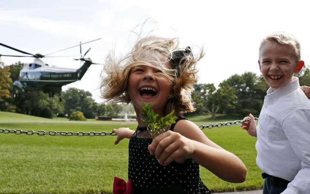 Brooke Fiddes, 5, and her brother Carter Fiddes, 9, both from Charlotte, N.C., react from the rotor wash of Marine One as President Donald Trump departs the South Lawn of the White House, Tuesday, September 26, 2017, in Washington. Trump is headed to New York. (Photo by Alex Brandon/AP Photo)
