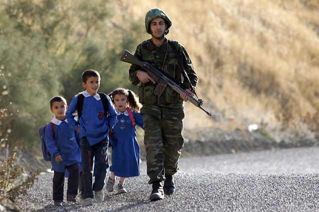 A Turkish soldier, flanked by children on their way to school, patrols on a road in the province of Sirnak, near the Turkish-Iraqi border, southeastern Turkey, 17 October 2007. (Photo by Mustafa Ozer/AFP Photo)
