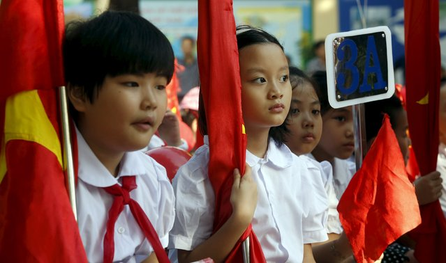 Girls hold national flags while they attend the opening ceremony of the new school year at a school in Hanoi September 5, 2015. Schools in Vietnam reopened on Saturday, with around 22 million children heading back to classrooms after a three-month summer break, local newspapers reported. (Photo by Reuters/Kham)