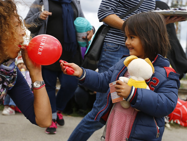 A volunteer gives a balloon to a migrant child at the railway station in Nickelsdorf, Austria September 6, 2015. (Photo by Leonhard Foeger/Reuters)