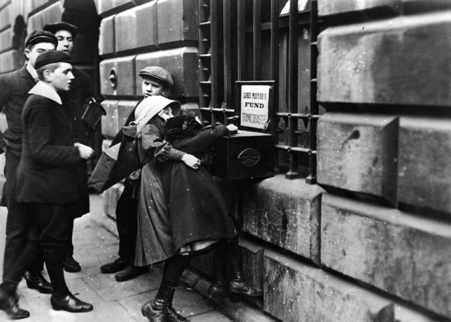 """Chidren putting money into a collection box in aid of victims of the """"Titanic"""" disaster, outside Mansion House, London, 1912. (Photo by Hulton Archive)"""