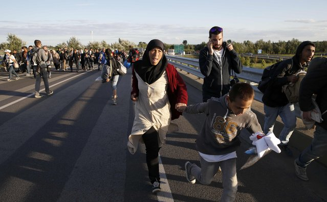 Migrants run against the traffic on a motorway leading to Budapest as they escape a transit camp in the village of Roszke, Hungary, September 7, 2015. (Photo by Marko Djurica/Reuters)