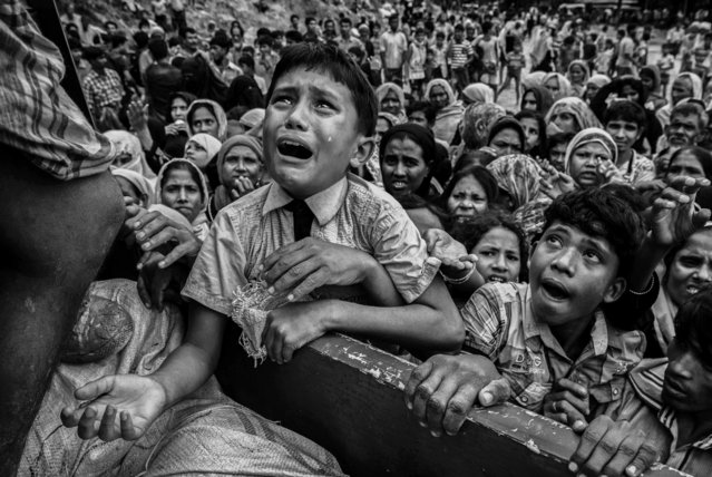 A Rohingya refugee boy desperate for aid cries as he climbs on a truck distributing aid for a local NGO near the Balukali refugee camp on September 20, 2017 in Cox's Bazar, Bangladesh. (Photo by Kevin Frayer/Getty Images)