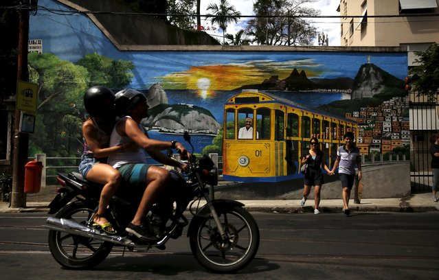 People pass a wall mural depicting a bonde, the typical tram line in Santa Teresa neighborhood in Rio de Janeiro, Brazil, September 10, 2015. (Photo by Pilar Olivares/Reuters)