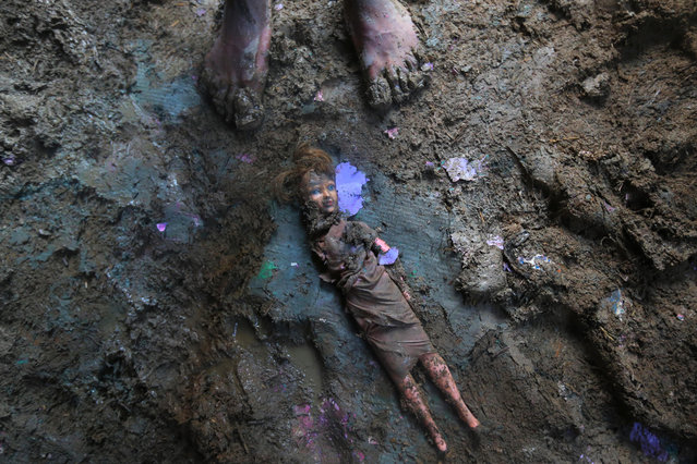 A Kashmiri stands near a doll smeared with mud inside a flood damaged house in Srinagar,  India, Friday, September 19, 2014. The floods engulfed much of Kashmir two weeks ago, leaving hundreds of thousands of people homeless in both the Indian- and Pakistani-administered areas of the disputed territory. (Photo by Dar Yasin/AP Photo)