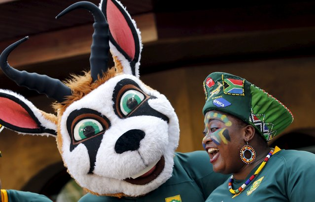 A rugby fan gestures next to a mascot during a public farewell for South Africa's rugby team, ahead of their departure for the World Cup in England, in Johannesburg September 11, 2015. South Africa Rugby Union president Oregan Hoskins has defended his administration's record in providing opportunities to non-white players at the highest level and urged the country to get behind the team for the World Cup. (Photo by Siphiwe Sibeko/Reuters)