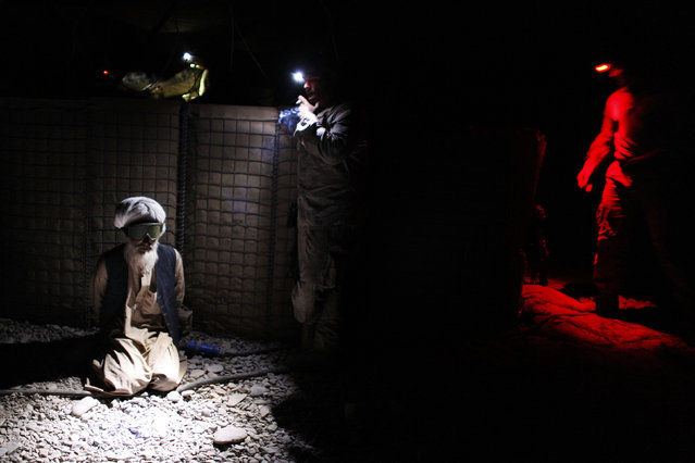 An Afghan man is detained by U.S. Marines from the First Battalion, Eighth Marines Bravo Company at their base in Talibjan after a battle against Taliban insurgents in Musa Qala district in southern Afghanistan's Helmand province November 7, 2010. (Photo by Finbarr O'Reilly/Reuters)