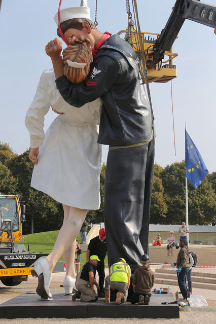 """Workers hoist and lock together pieces of """"Unconditional Surrender"""", an 8-meter (25-foot) cast-bronze sculpture in color of a sailor and a nurse in lip-locked embrace, outside the Caen Memorial in Normandy, France, Tuesday, September 23, 2014. The sculpture by Seward Johnson is based on a U.S. (Photo by David Vincent/AP Photo)"""