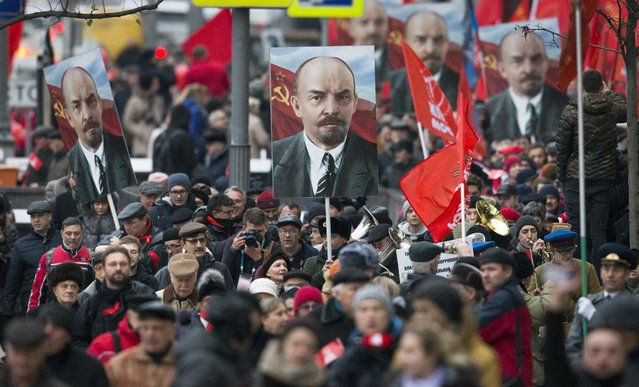 Communist party supporters carry portraits of Soviet founder Vladimir Lenin during a demonstration marking the 100th anniversary of the 1917 Bolshevik revolution in Moscow, Russia, Tuesday, November 7, 2017. Thousands of Communist demonstrators marked the centennial of the 1917 Bolshevik revolution Tuesday by marching across downtown Moscow. (Photo by Alexander Zemlianichenko/AP Photo)