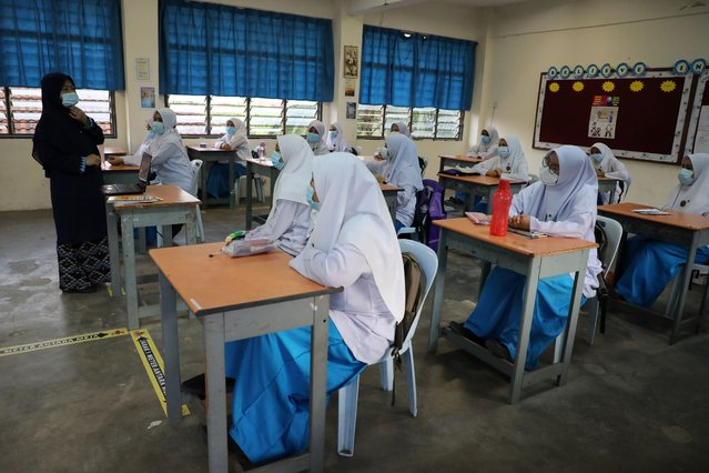 A teacher speaks to students during a class at a secondary school, as schools reopen amid the coronavirus disease (COVID-19) outbreak, in Shah Alam, Malaysia on June 24, 2020. (Photo by Lim Huey Teng/Reuters)