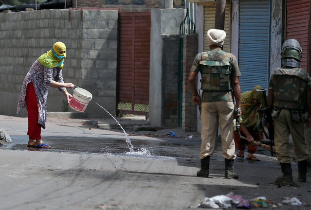 Women wash the street outside their house in Srinagar as security forces patrol during a curfew following weeks of violence in Kashmir August 19, 2016. (Photo by Cathal McNaughton/Reuters)