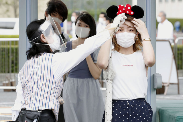 A visitor has her body temperature checked at the entrance of Tokyo Disneyland in Urayasu, near Tokyo, Wednesday, July 1, 2020. Tokyo Disneyland reopened for the first time in four months after suspending operations due to coronavirus concerns. (Photo by Kyodo News via AP Photo)