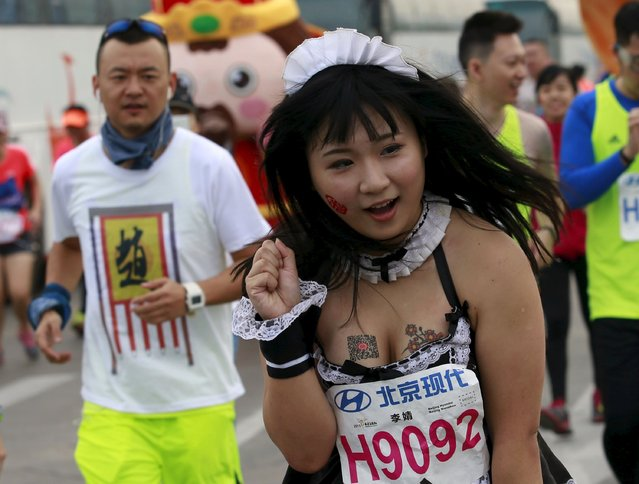 A woman wearing a maid's costume runs in the Beijing International Marathon in Beijing, China, September 20, 2015. (Photo by Kim Kyung-Hoon/Reuters)