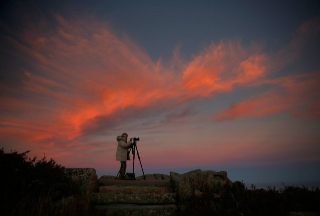 "Cindy Archbell photographs the landscape of Acadia National Park in Maine from the summit of Cadillac Mountain at sunset, Thursday, October 2, 2014. Archbell, of Culpepper, Va., is spending a week in the park pursuing her photographic hobby.  ""The first day I was here I spent 10 hours shooting"", she said. (Photo by Robert F. Bukaty/AP Photo)"