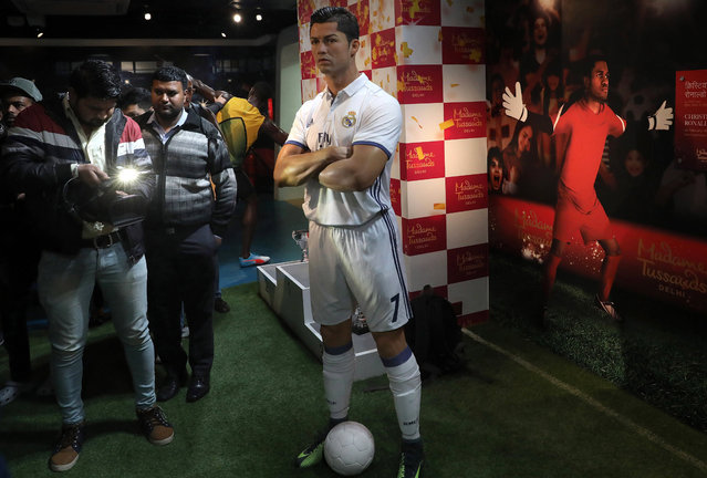 Indian journalists stand near a wax figure of Portuguese soccer player Cristiano Ronaldo at the Madame Tussauds wax museum in New Delhi, India, 30 November 2017. (Photo by Rajat Gupta/EPA/EFE)