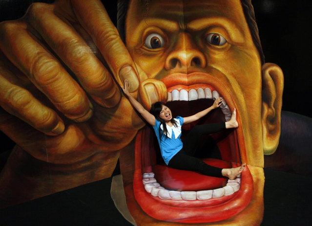 A visitor poses with a 3D art work during a Japanese Trick Art exhibition at a shopping mall in Jakarta, Indonesia, Tuesday, Dec. 4, 2012. (AP Photo/Dita Alangkara)