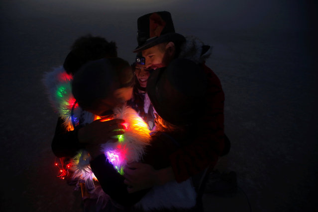 A group of participants huddle in a dust storm as approximately 70,000 people from all over the world gather for the 30th annual Burning Man arts and music festival in the Black Rock Desert of Nevada, U.S. September 1, 2016. (Photo by Jim Urquhart/Reuters)