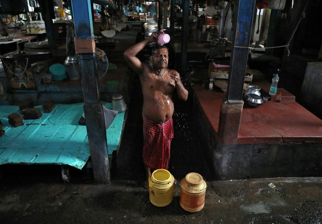 A vendor bathes inside a closed retail fish market after authorities announced lockdown for two days every week in the West Bengal state, amidst the spread of the coronavirus disease (COVID-19), in Kolkata, July 23, 2020. (Photo by Rupak De Chowdhuri/Reuters)